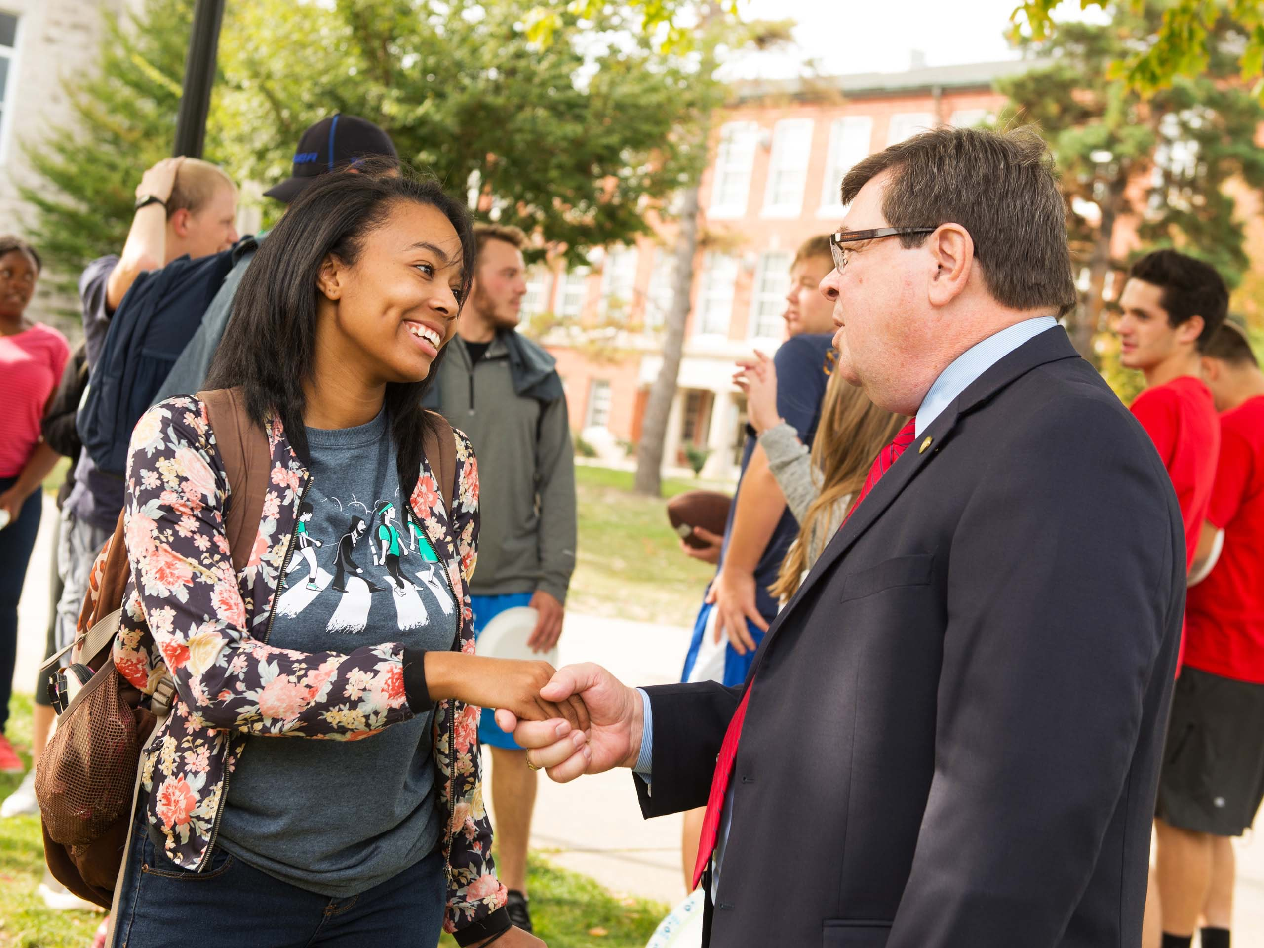 President Dietz shaking hands with a student.