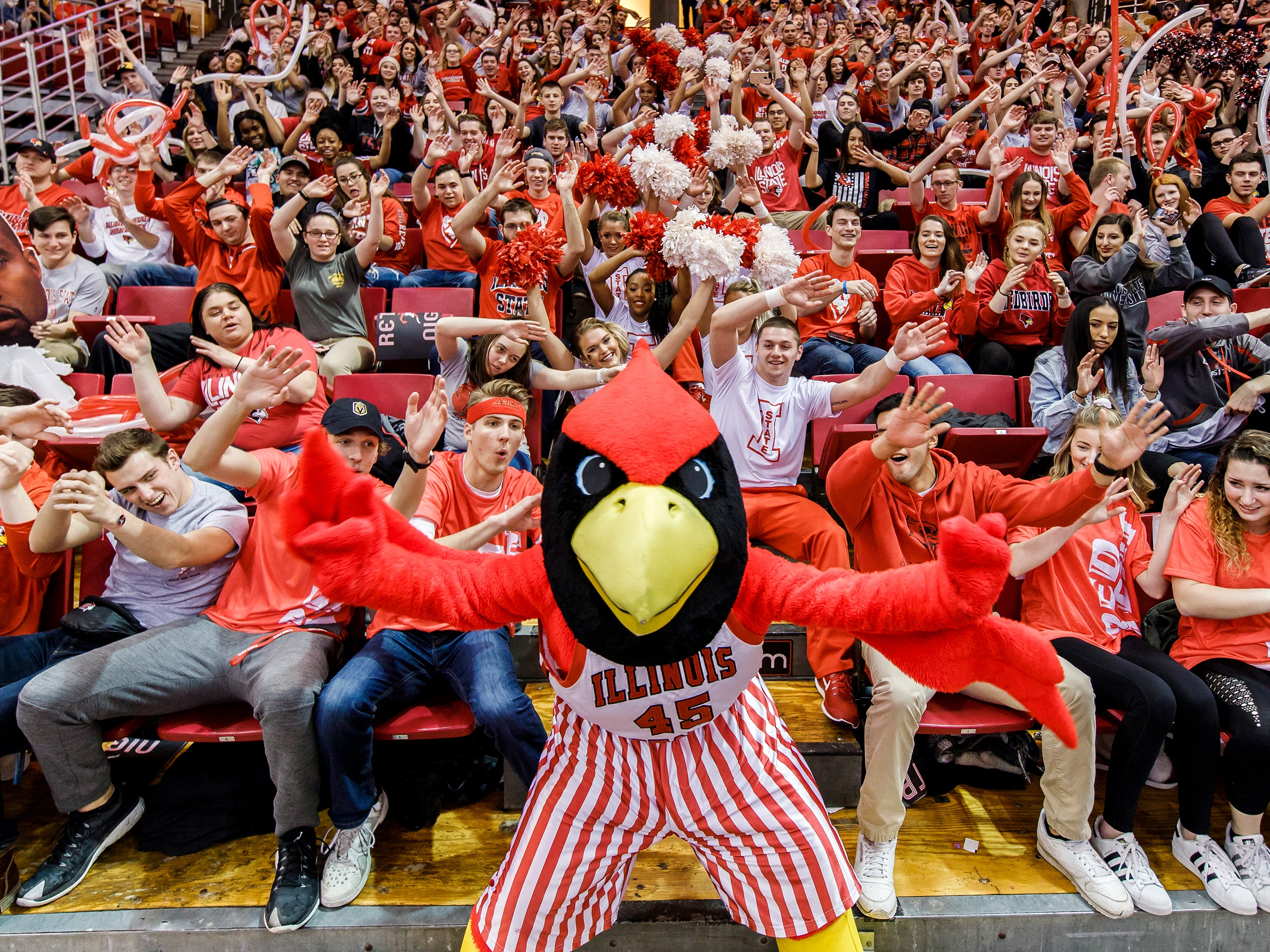 Reggie in front of a large crowd at Redbird Arena.