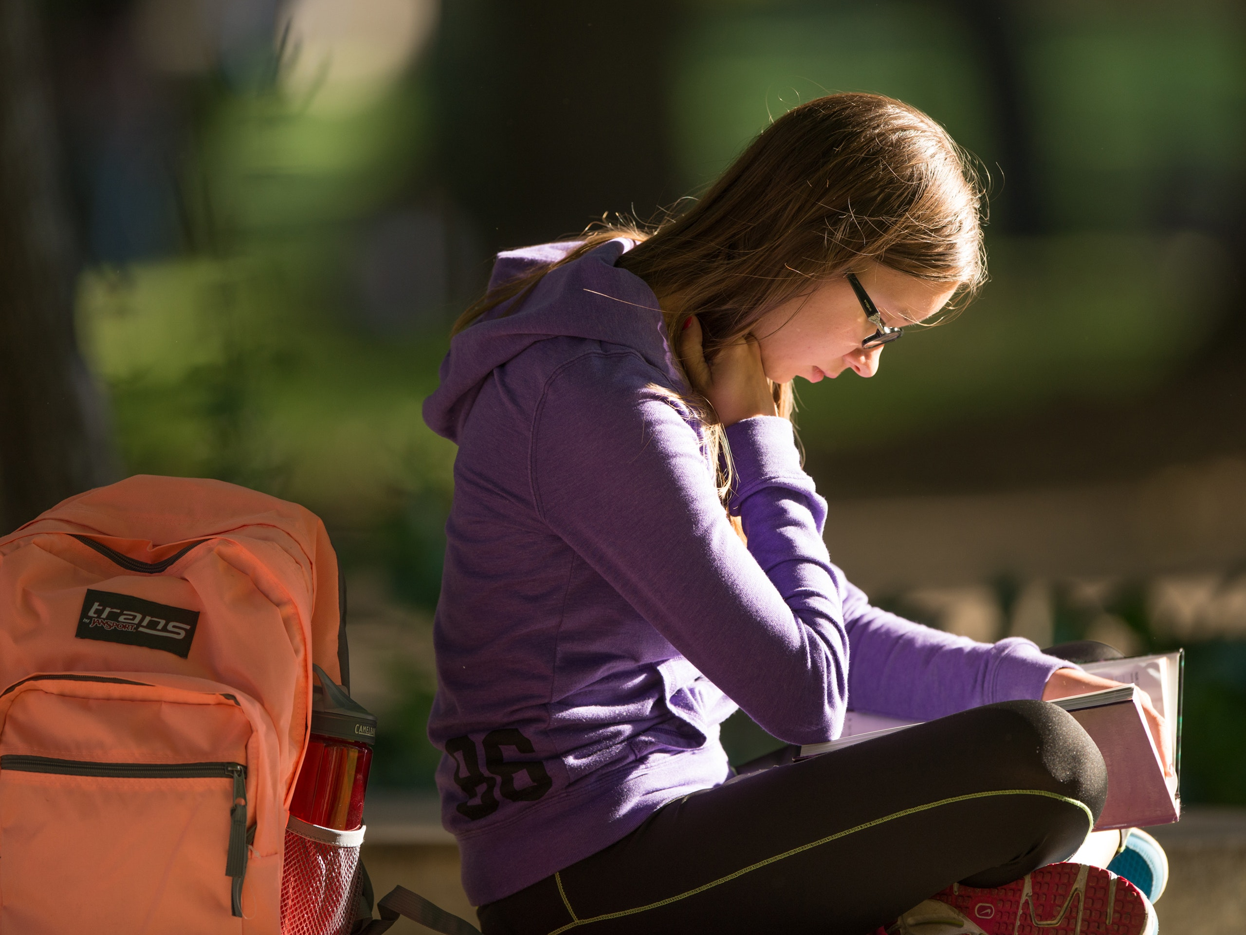Student sitting outside reading a textbook.