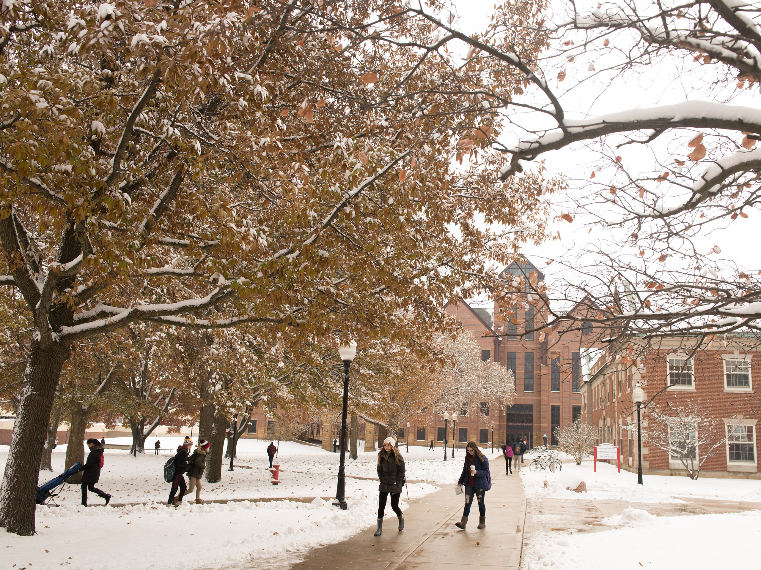 Students walking to and from class on the quad during the winter, with snow on the ground.