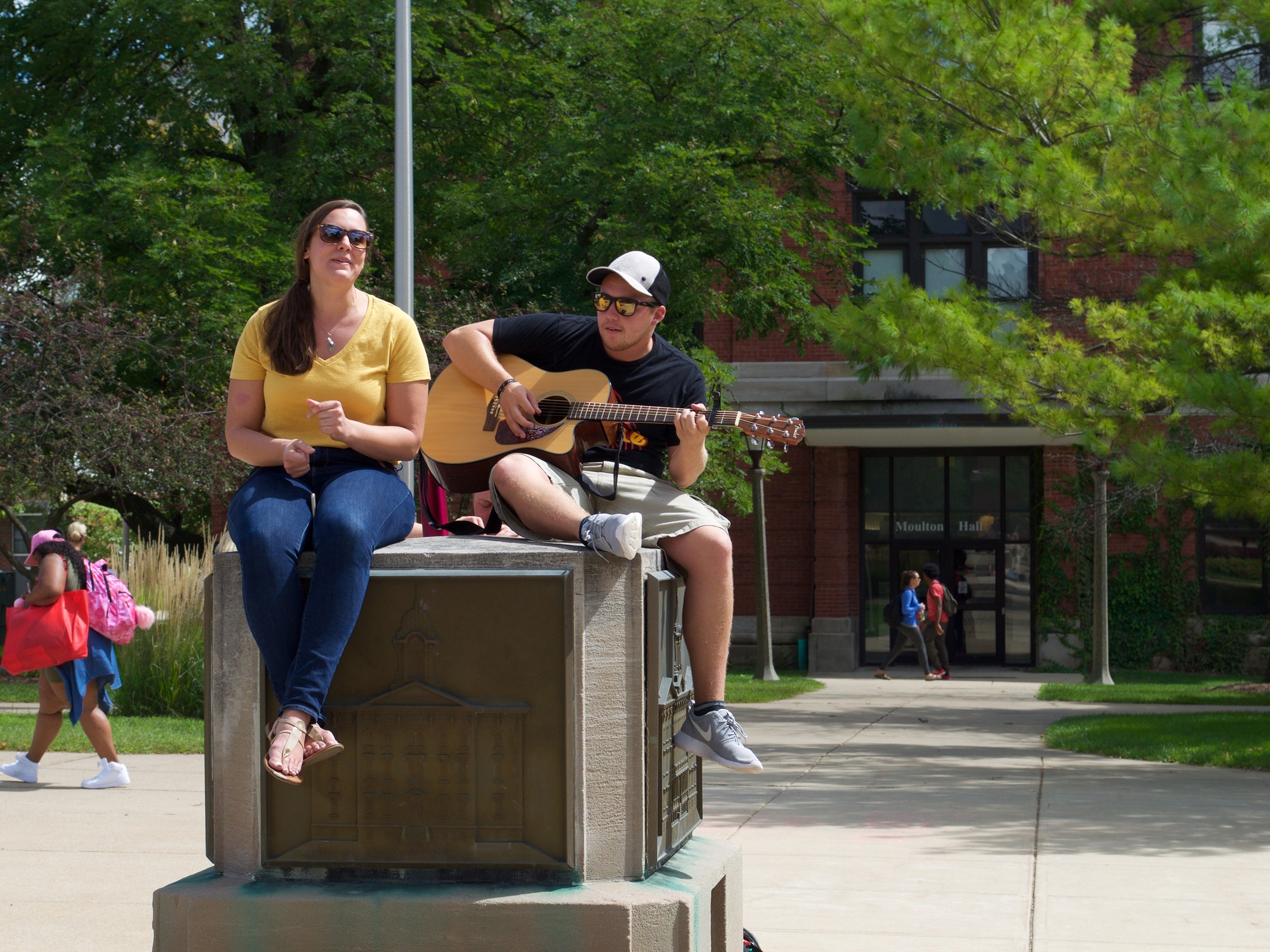 Two students singing and playing the guitar on the Old Main monument.