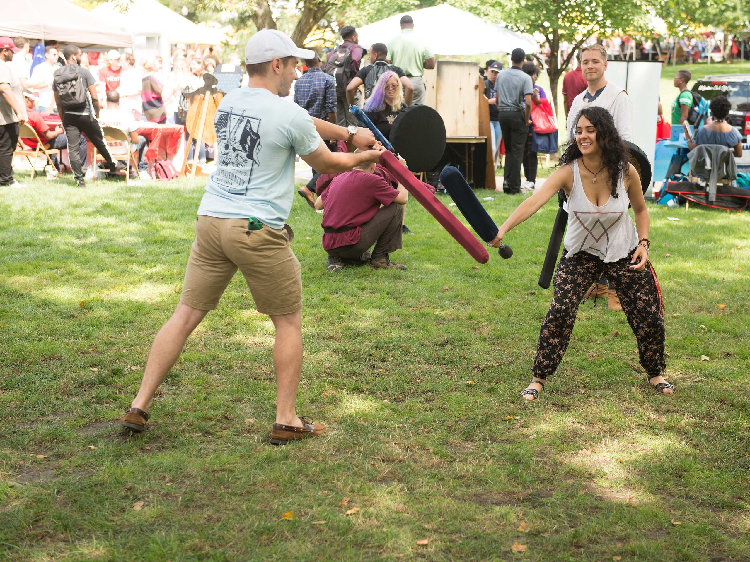 Male and female student fighting with foam swords on the quad during Festival ISU.