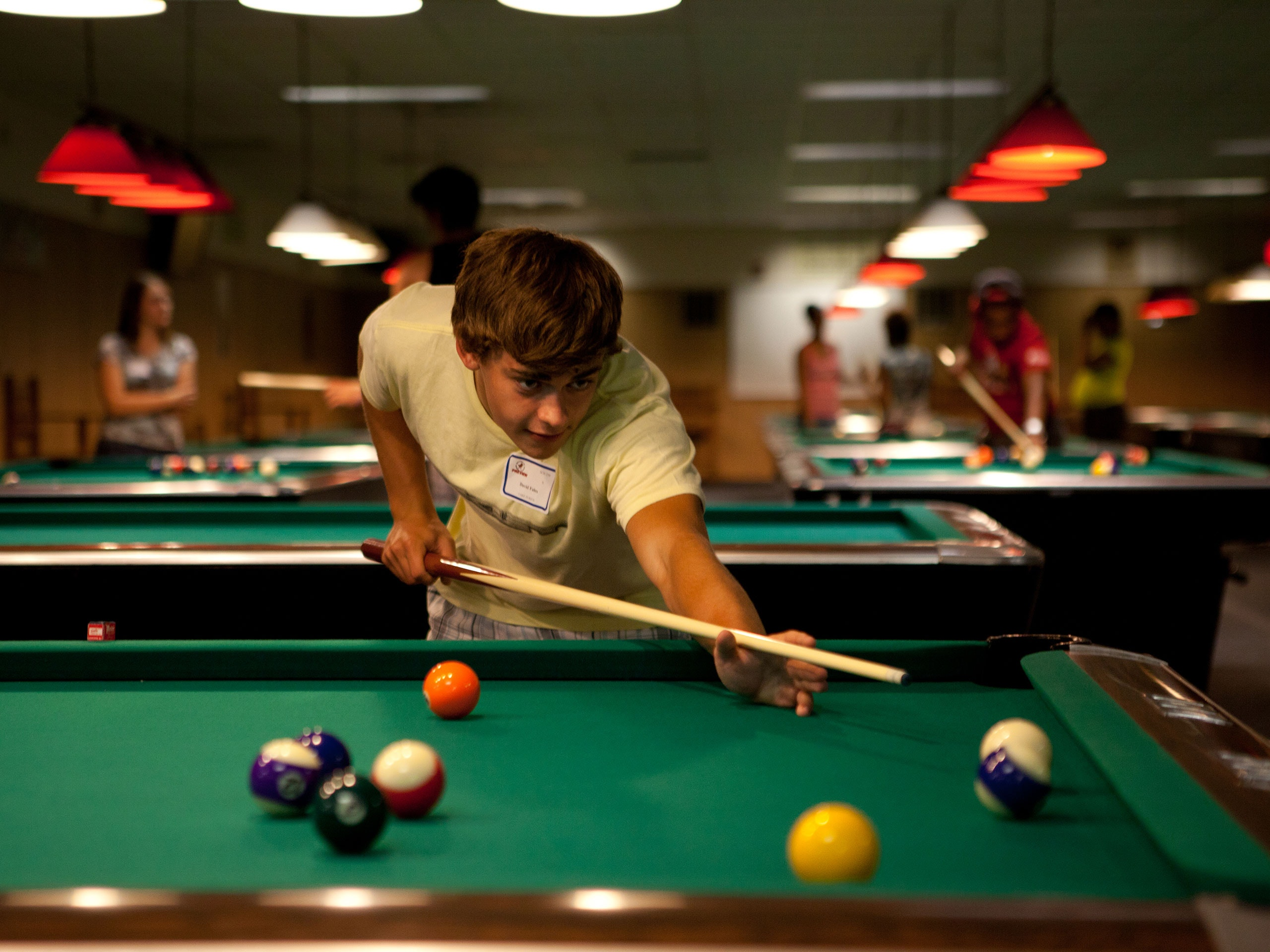 Male student playing pool in the Bone Student Center.