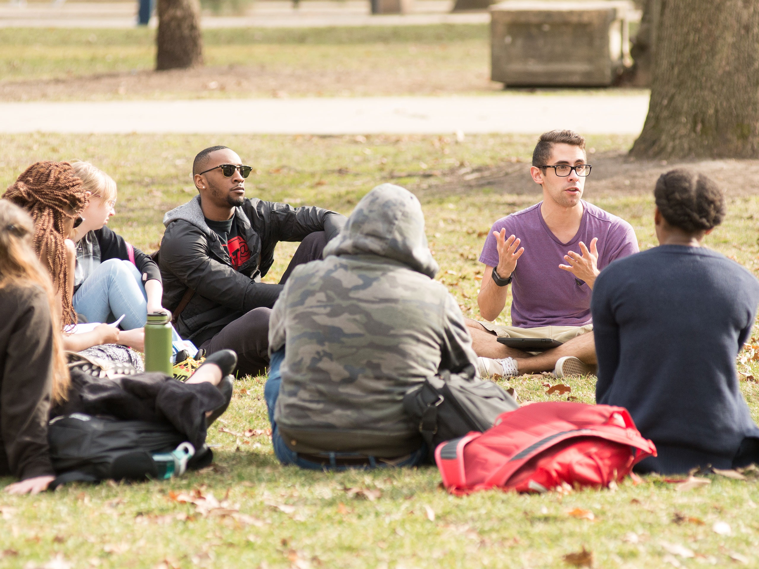 Group of dozen students sitting in a circle on the quad during a class.
