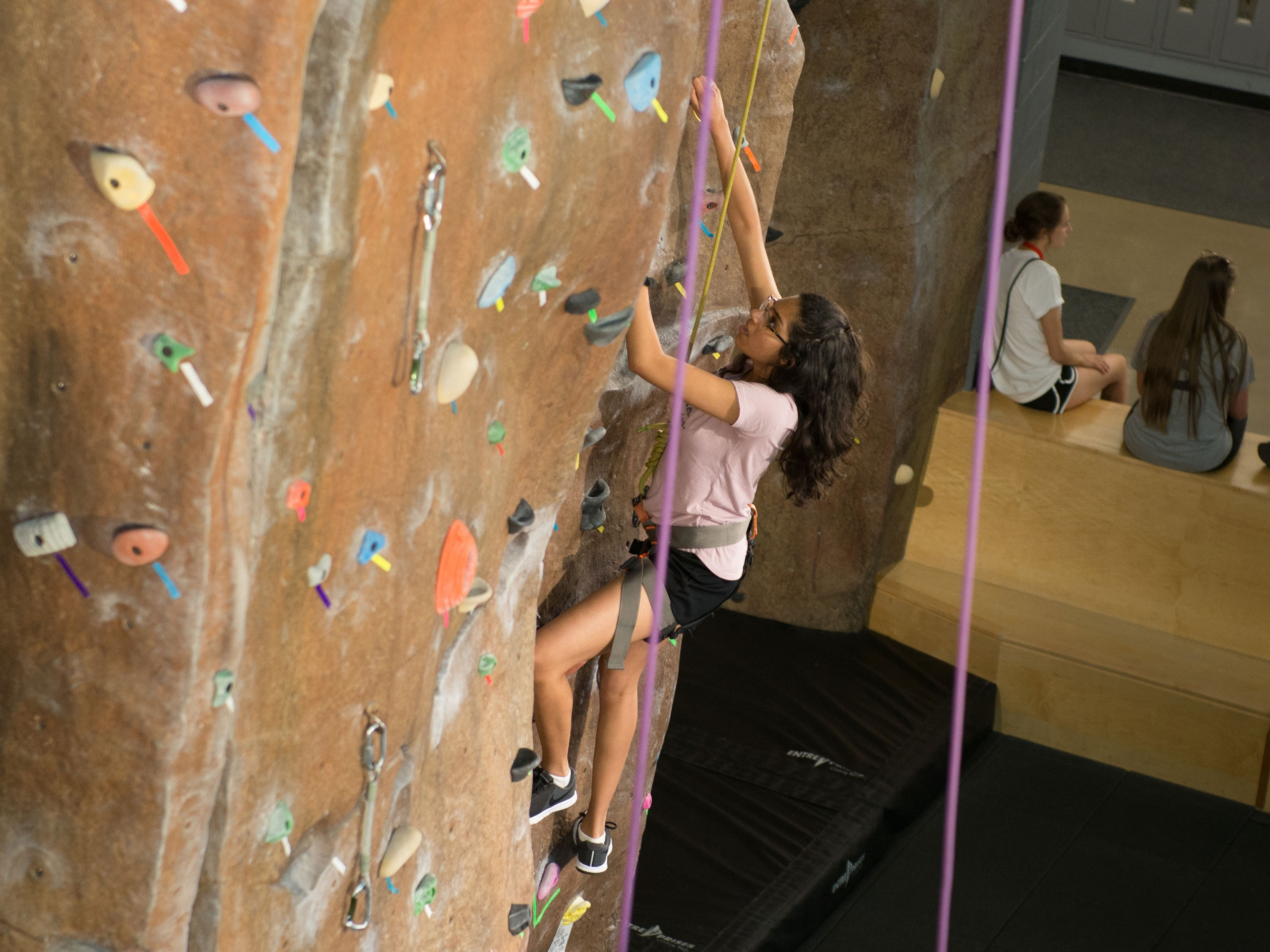 Female climbing the rock wall in the student fitness center.