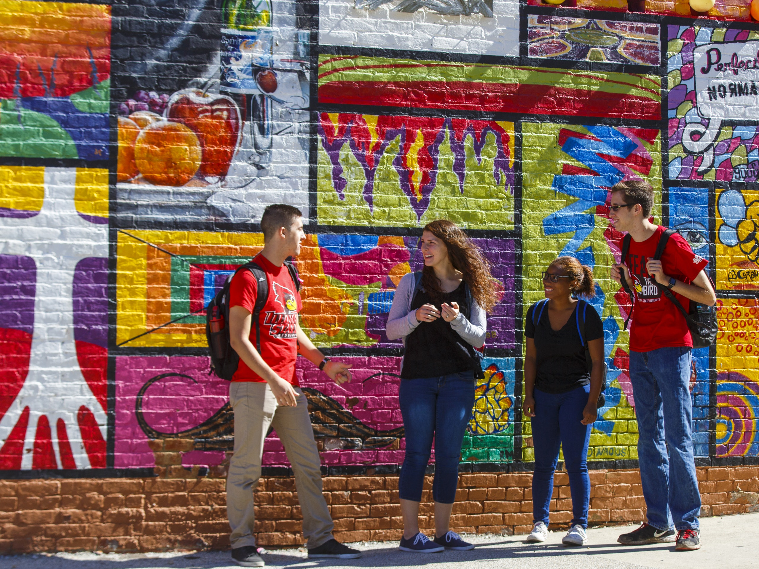 Students standing in front of a mural in Uptown Normal.