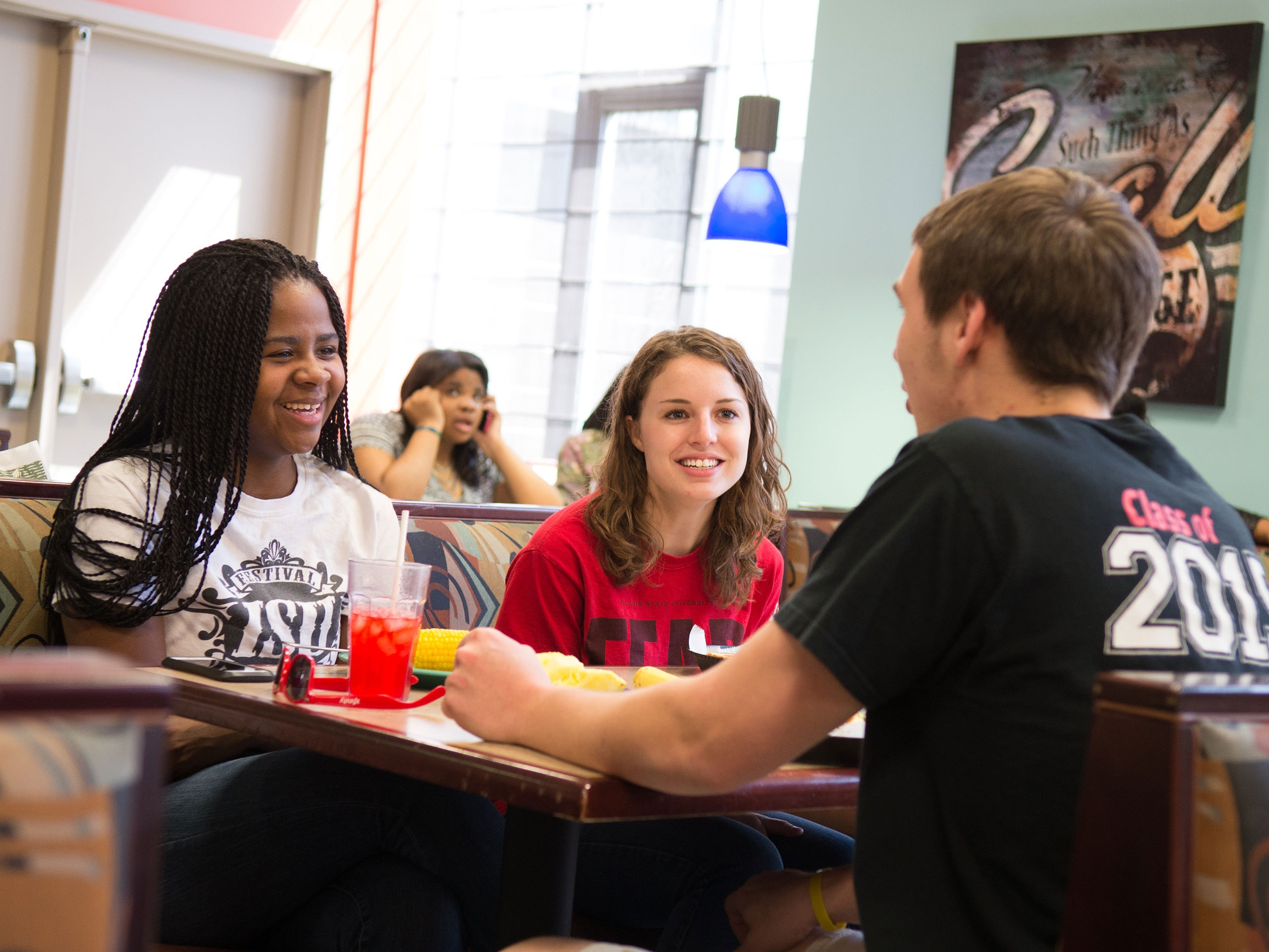 Students sitting in a dining center, talking during a meal.