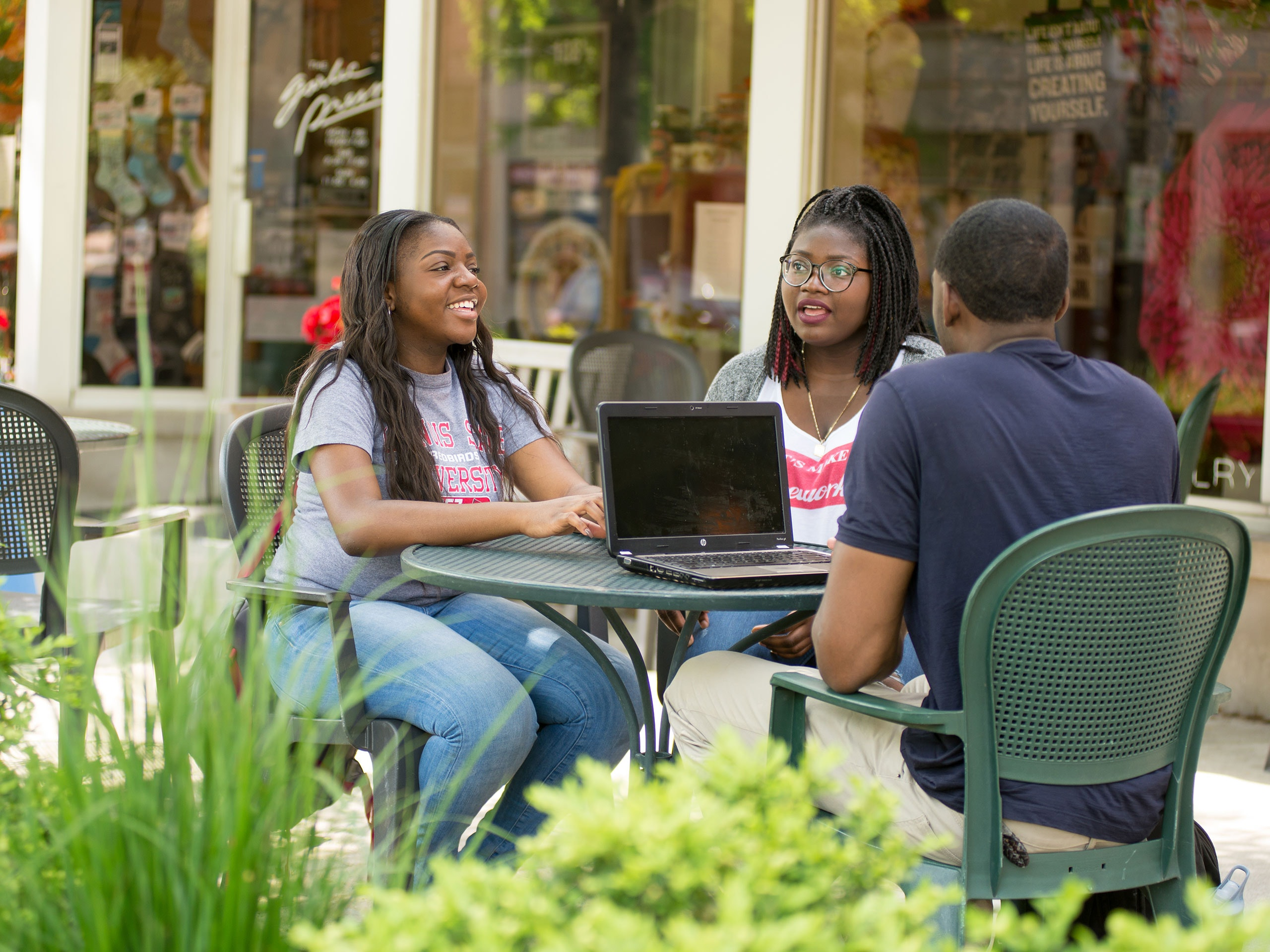 Three students sitting at an outdoor table in Uptown Normal.