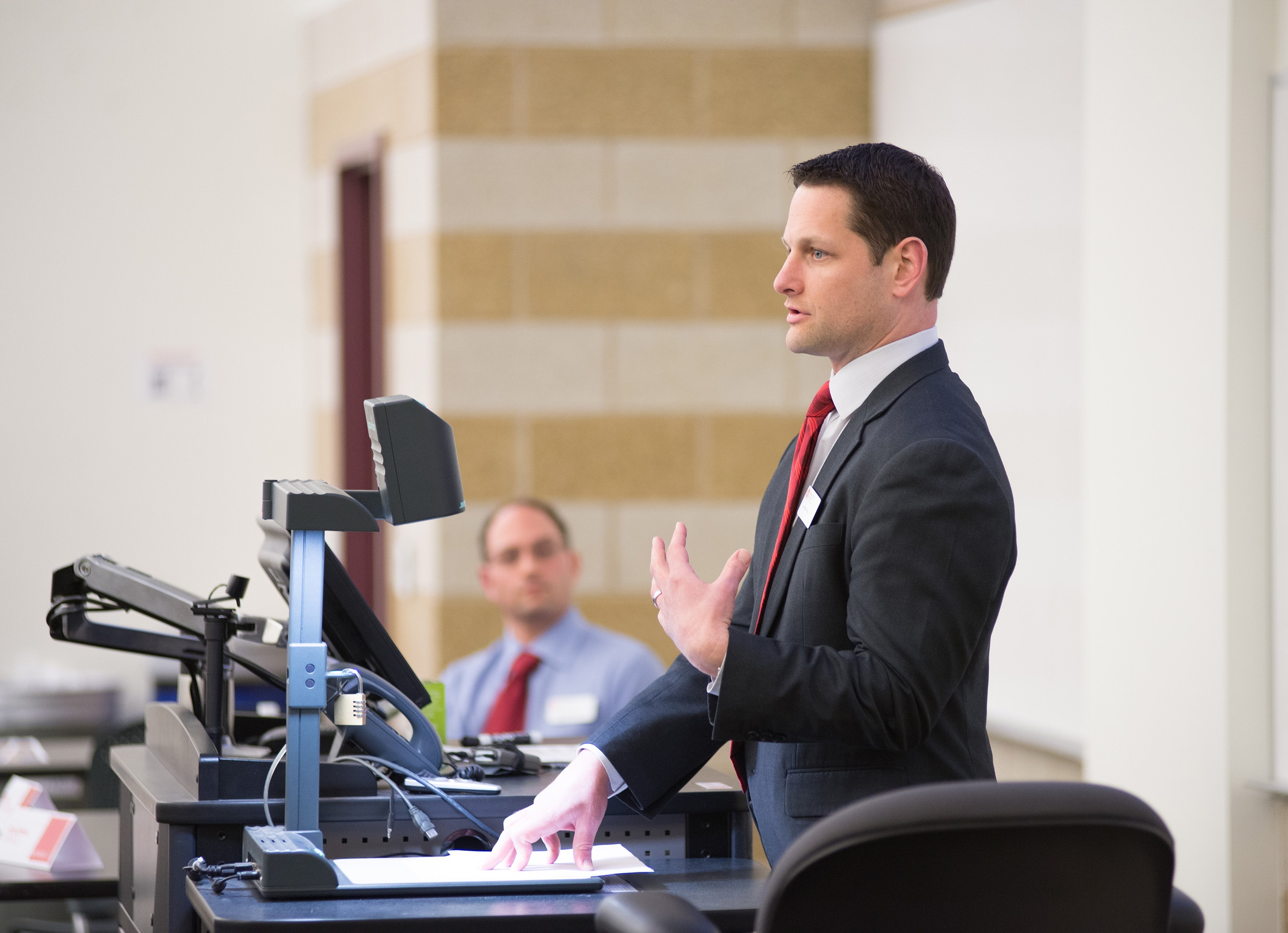 Male in suit presenting in a College of Business classroom.