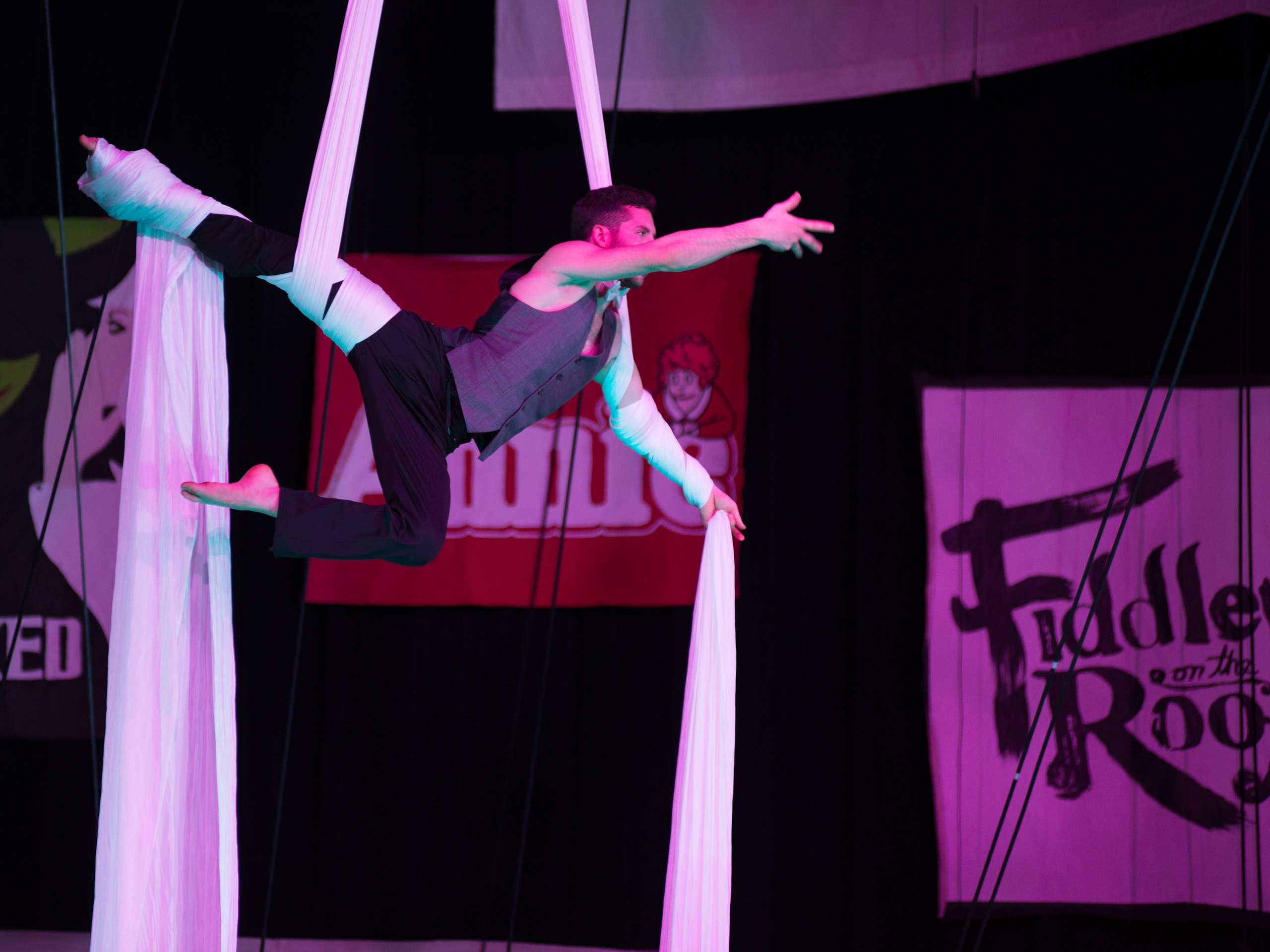 Male student hanging in silks during a Gamma Phi Circus performance.