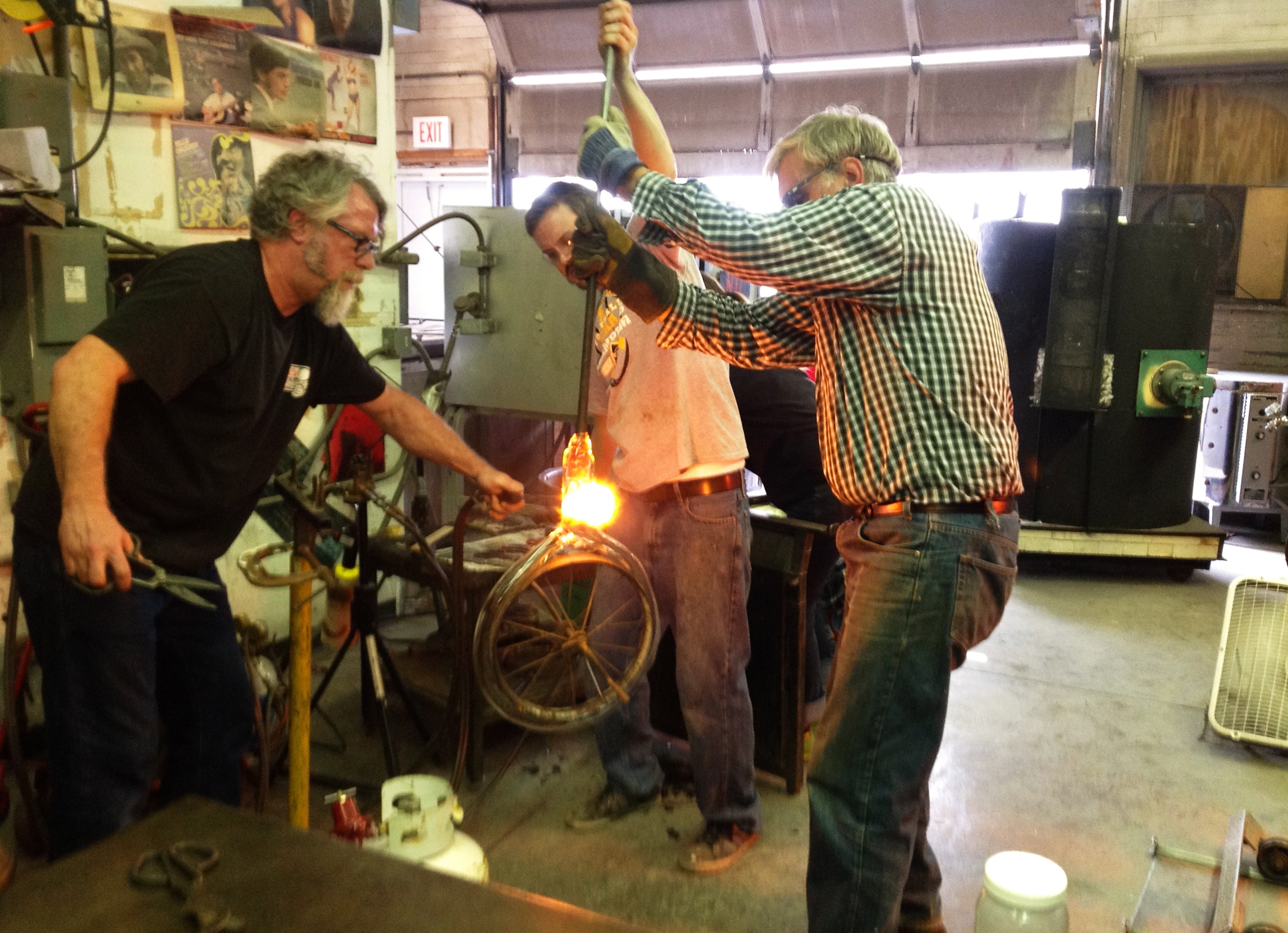 Robert DuGrenier working on a glass piece with faculty and students in the glass house.