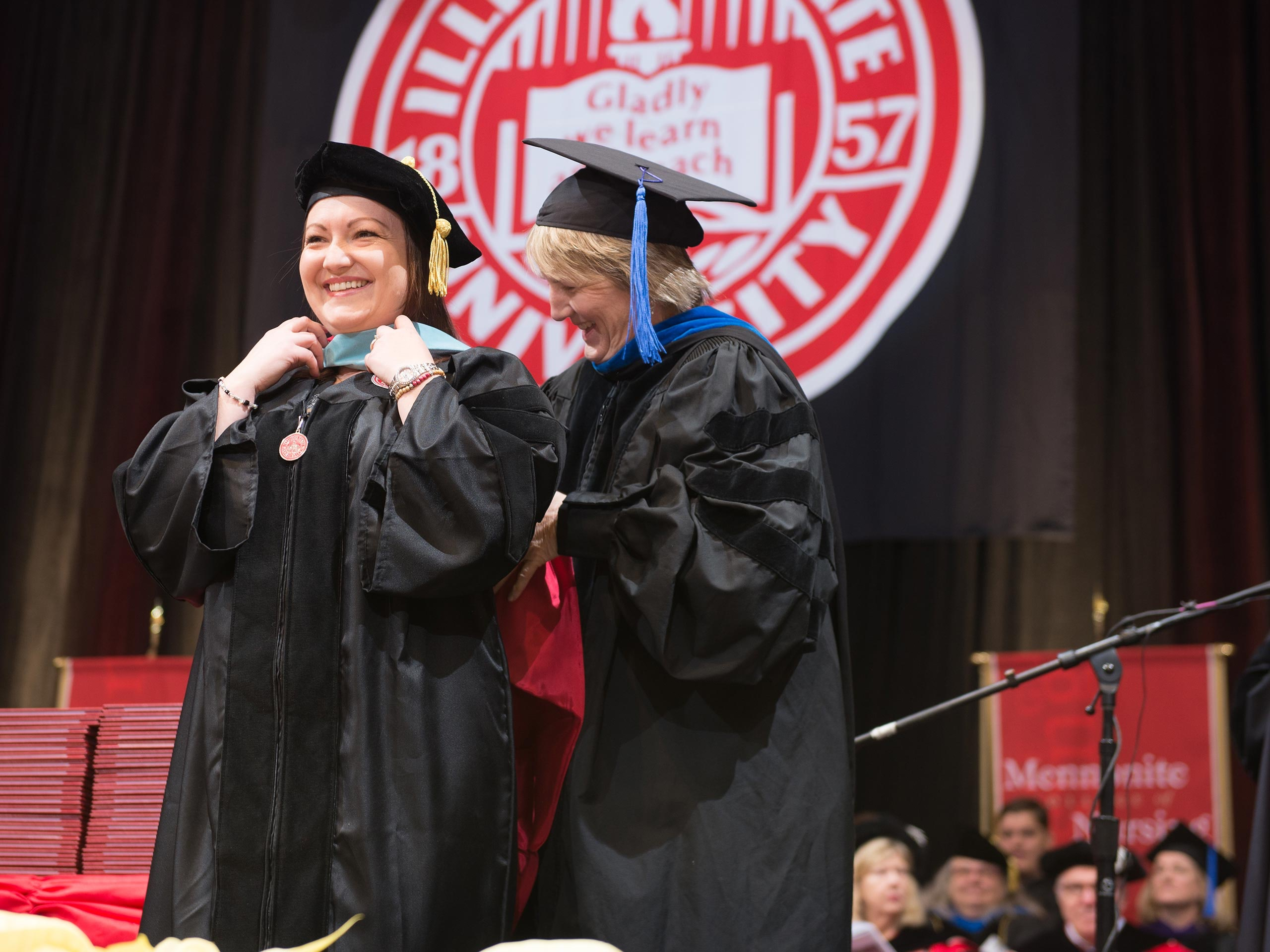 Female student getting graduate hood during commencement ceremony.