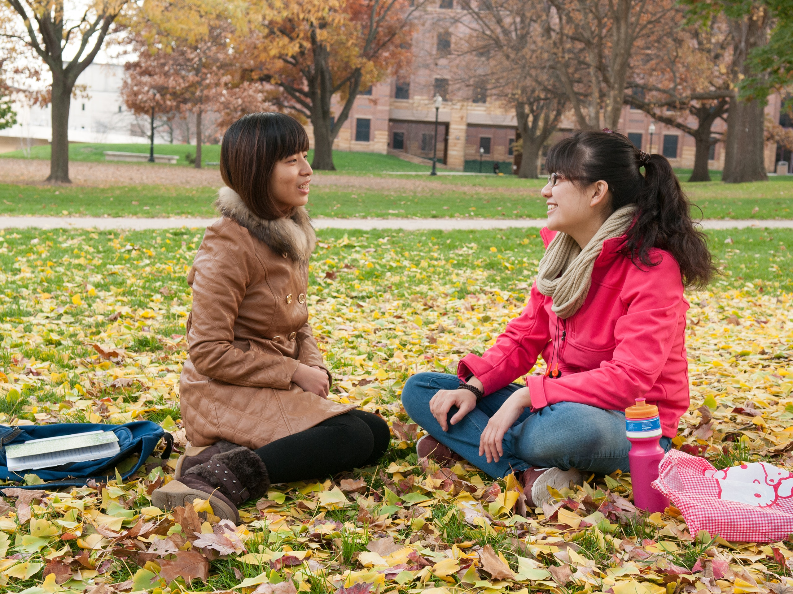 Two female asian students sitting on the quad with fall leaves on the ground.