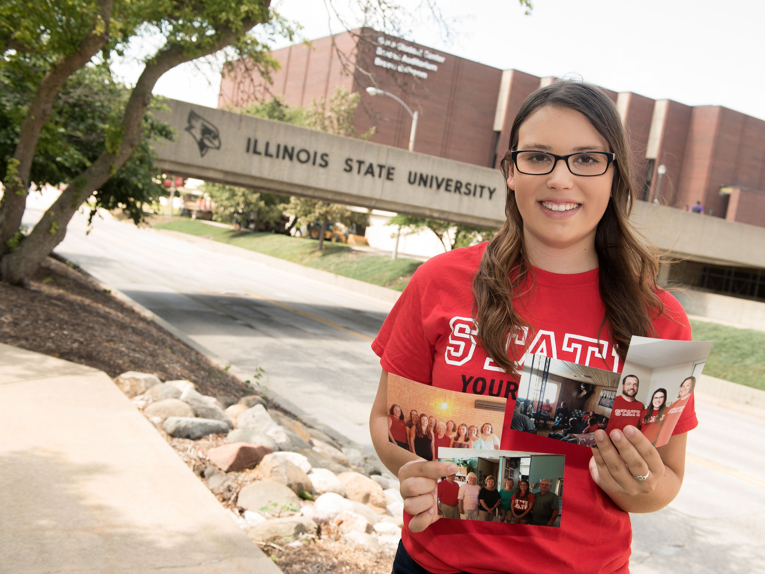 Katie Vickrey holding family photos in front of the College Avenue walkway.
