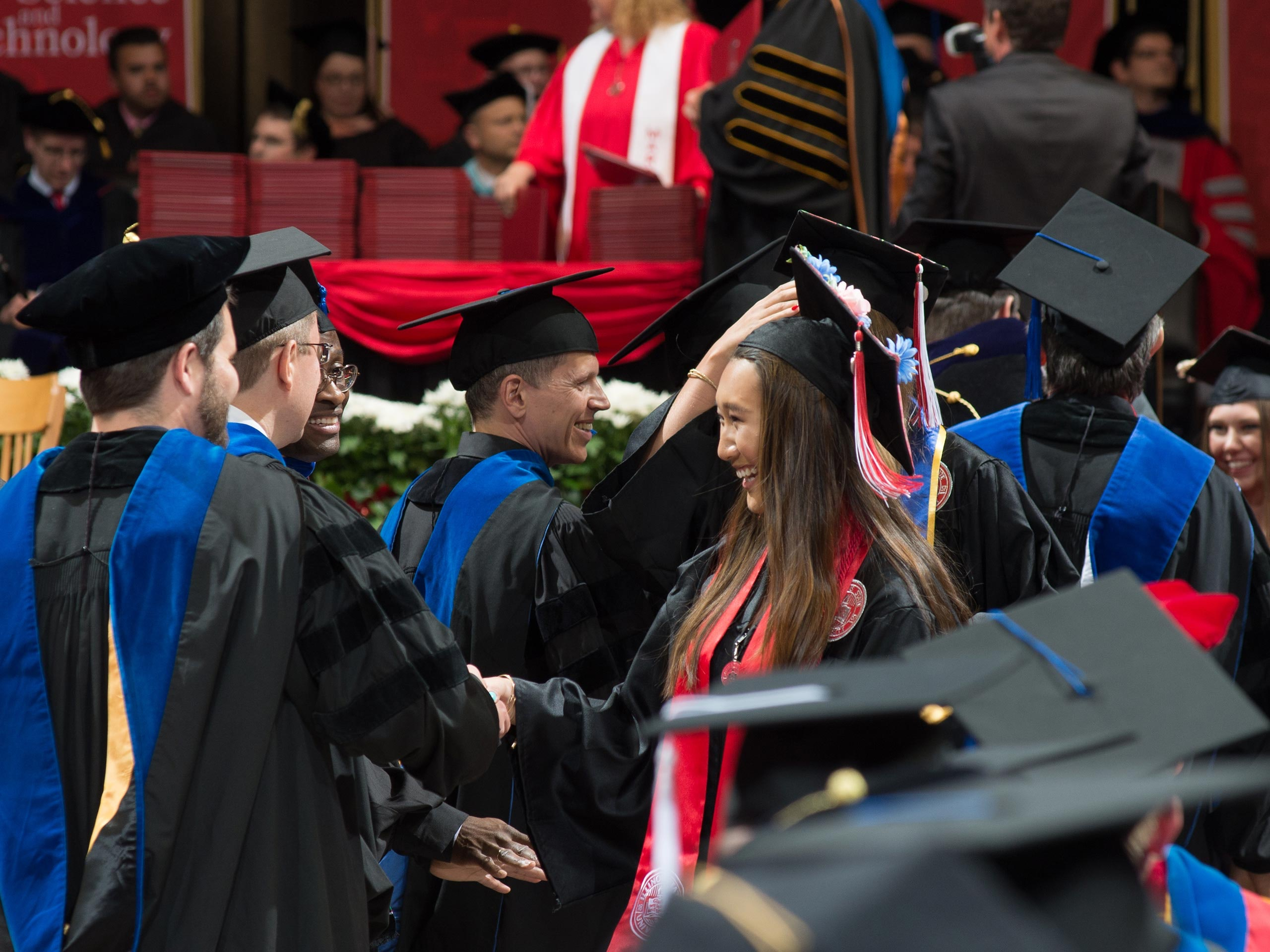 Female student shaking hands of faculty after receiving her diploma on stage.