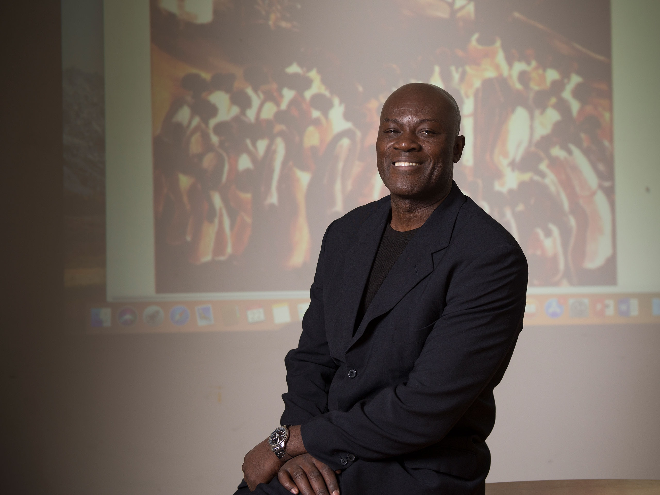 Angelo Kankande posing in front of a projected image.