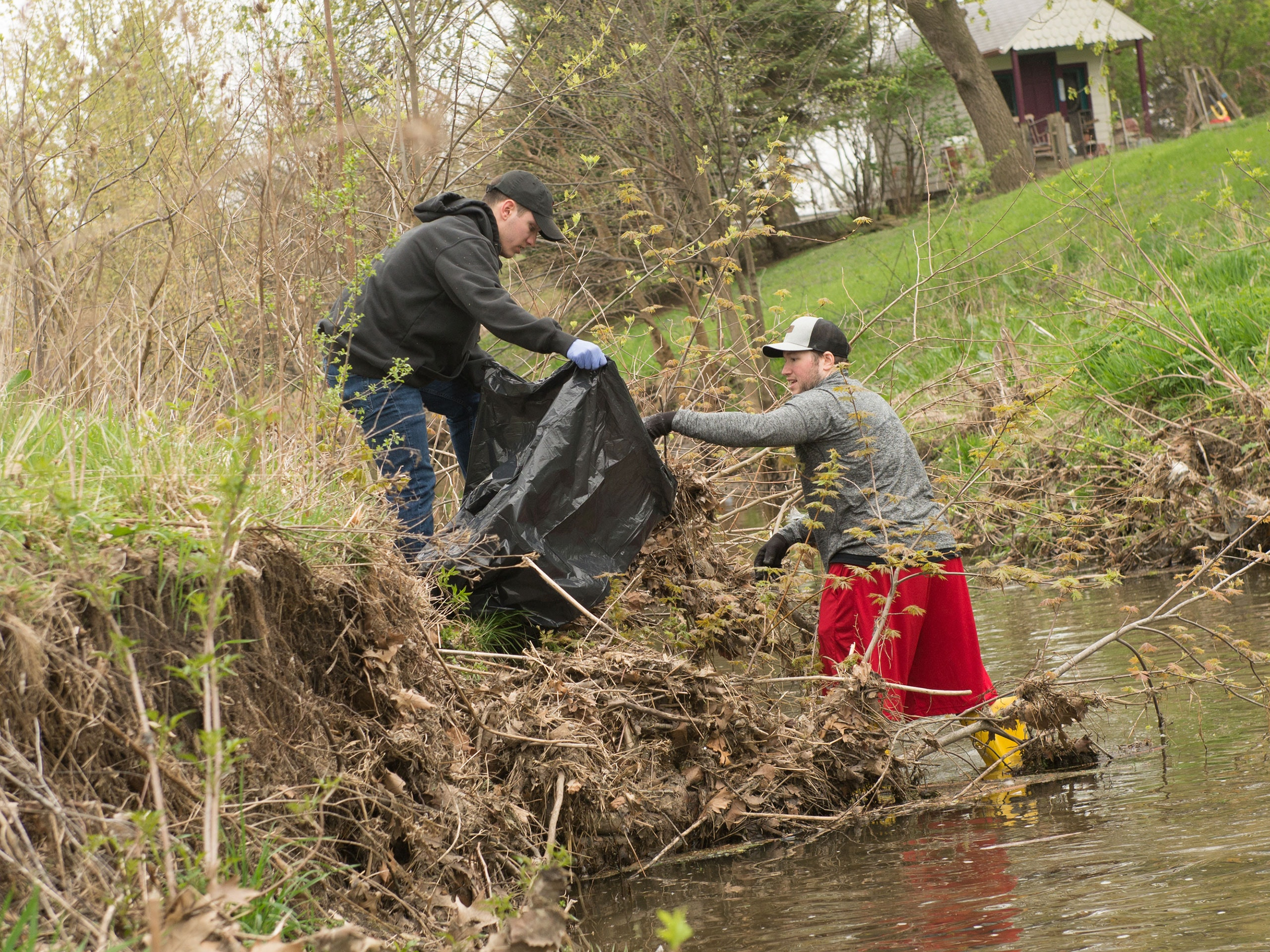 Male student standing in a creek placing garbage in a bag held by another male student on the creek edge.