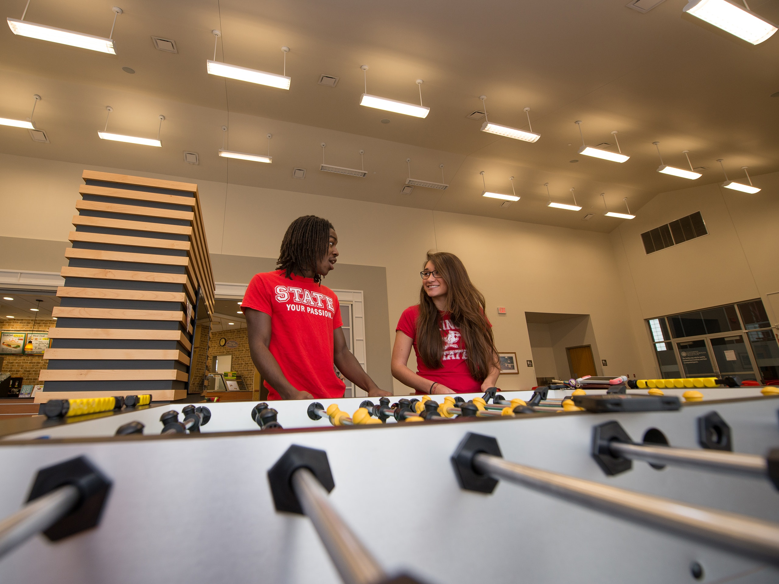 Male and female student team playing foosball in a residence hall common area.