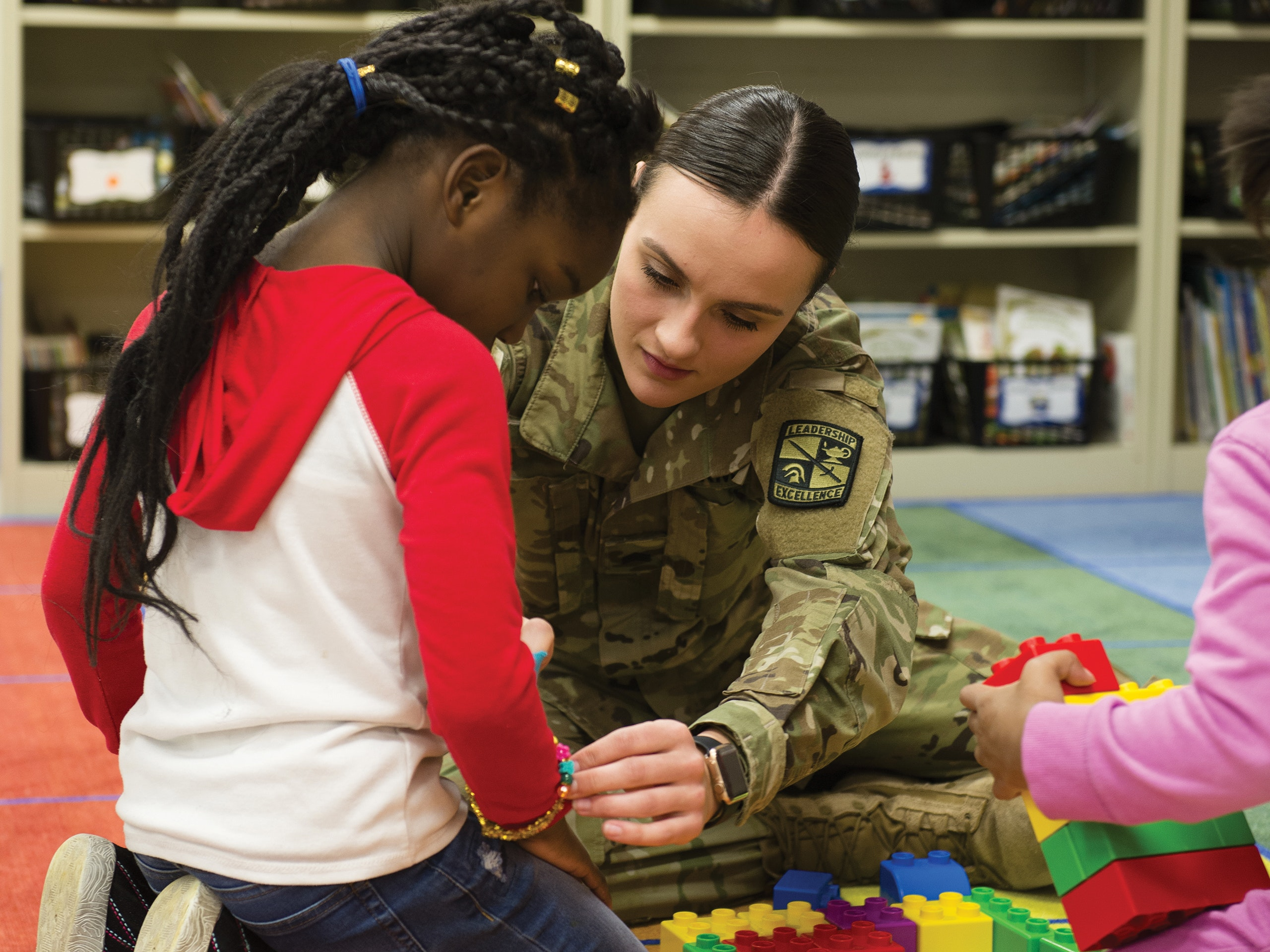 Female ROTC student in uniform helping a small girl on an elementary school classroom floor that is scattered with large Legos.