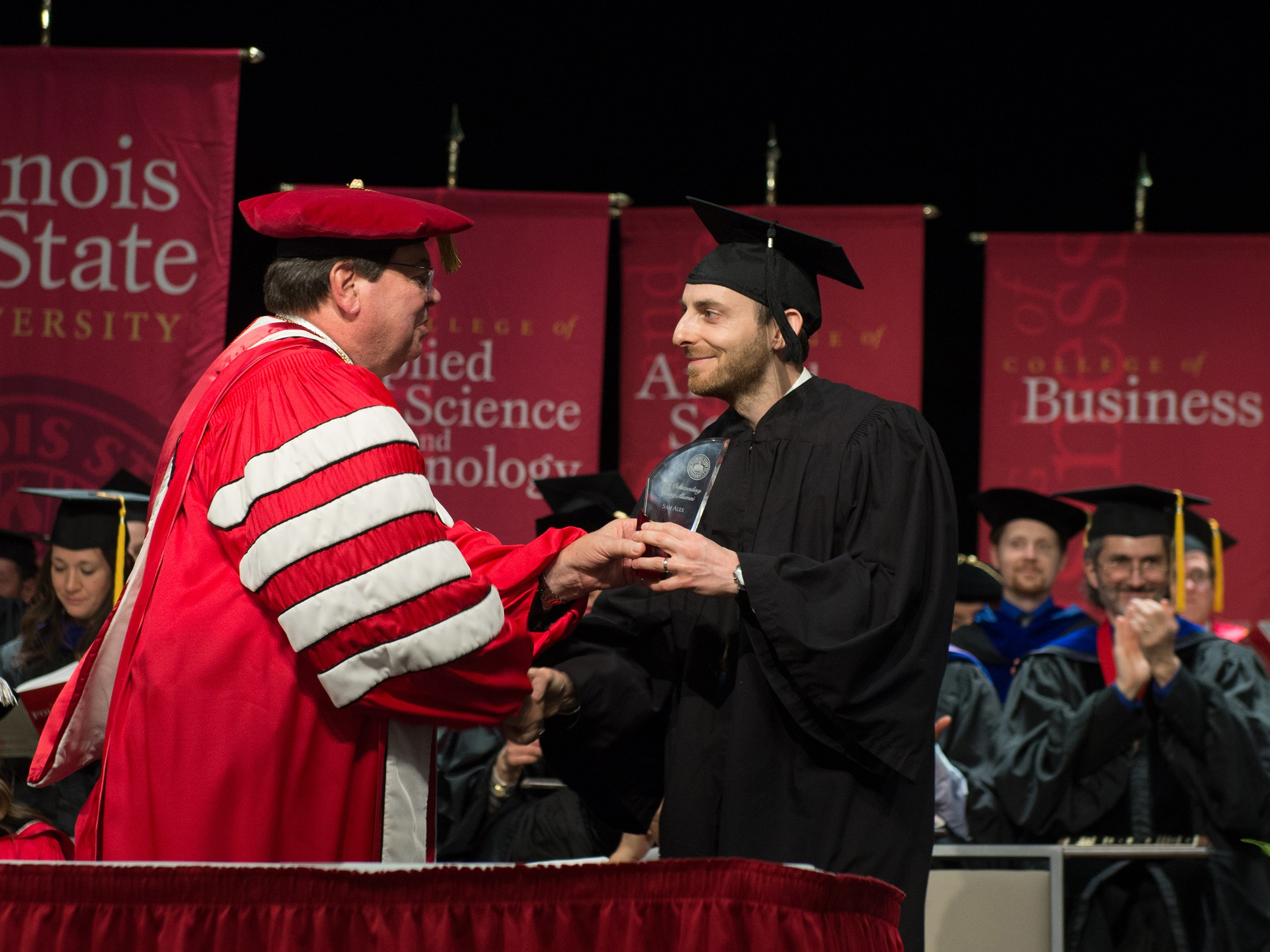 Sam Alex receiving an glass award from Dr. Dietz on a stage with everyone dressed in commencement gowns.