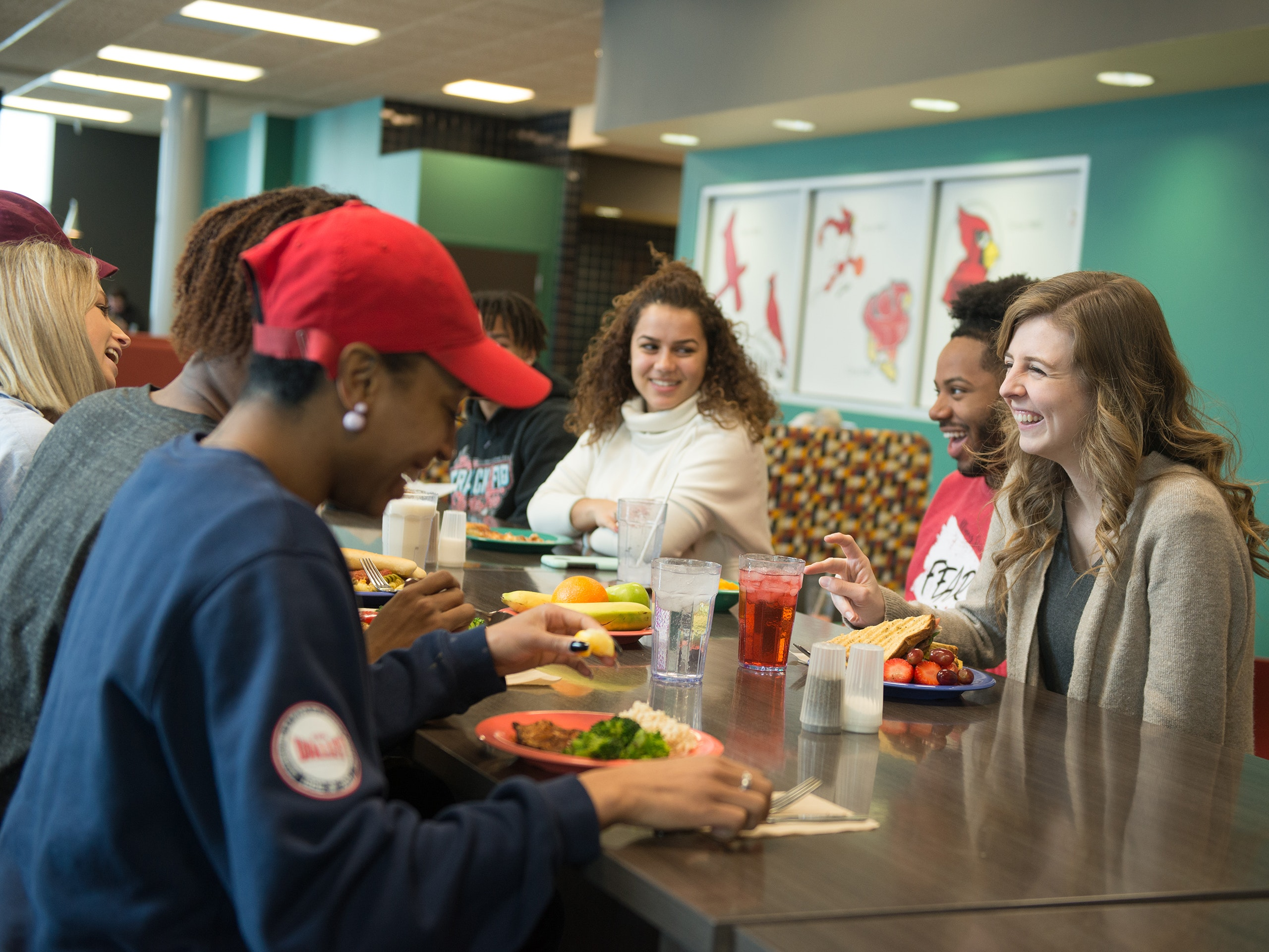 Group of students sitting at a table in a dining hall, chatting and laughing.