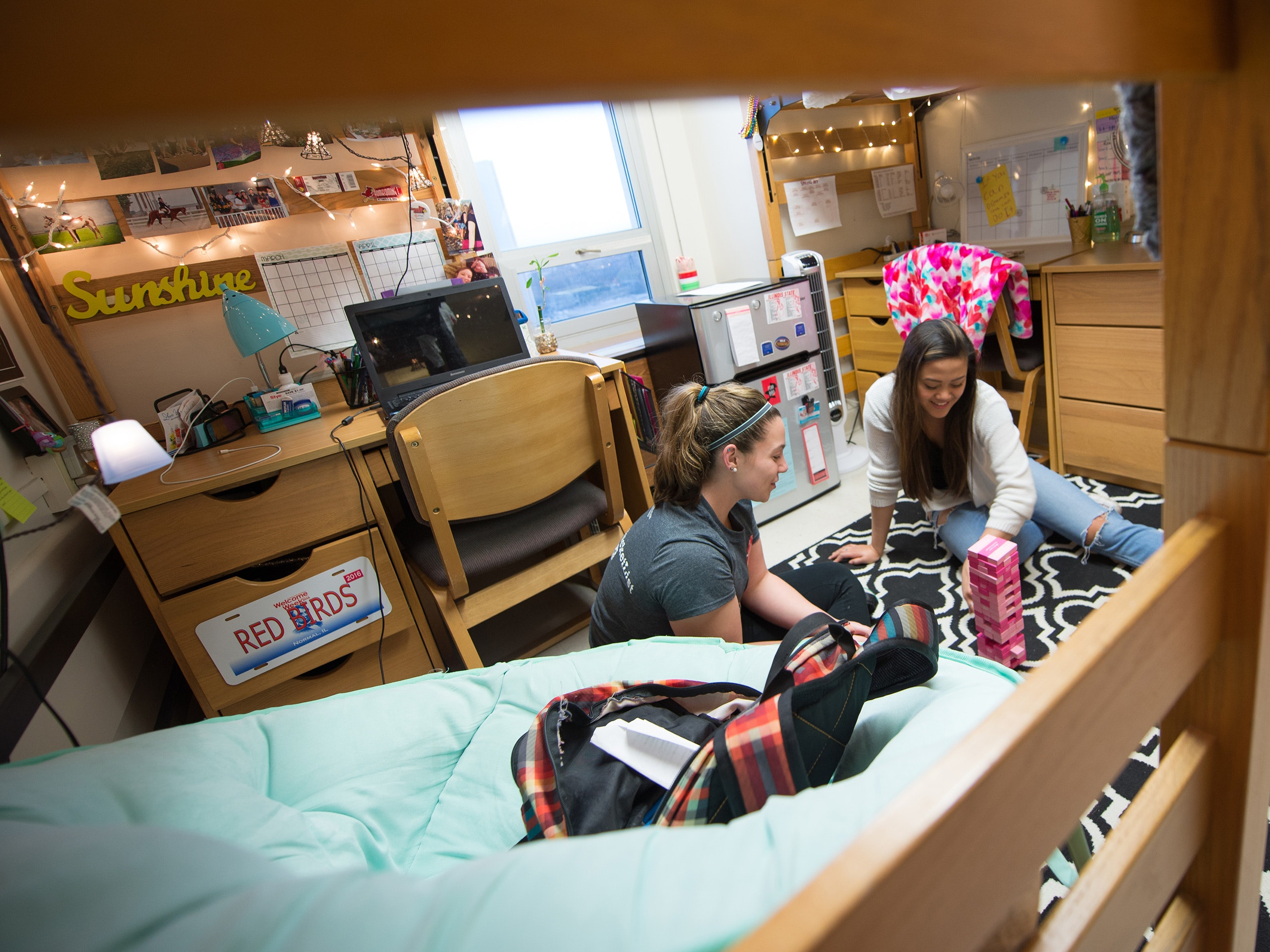 Two girls playing a game in their residence hall room.