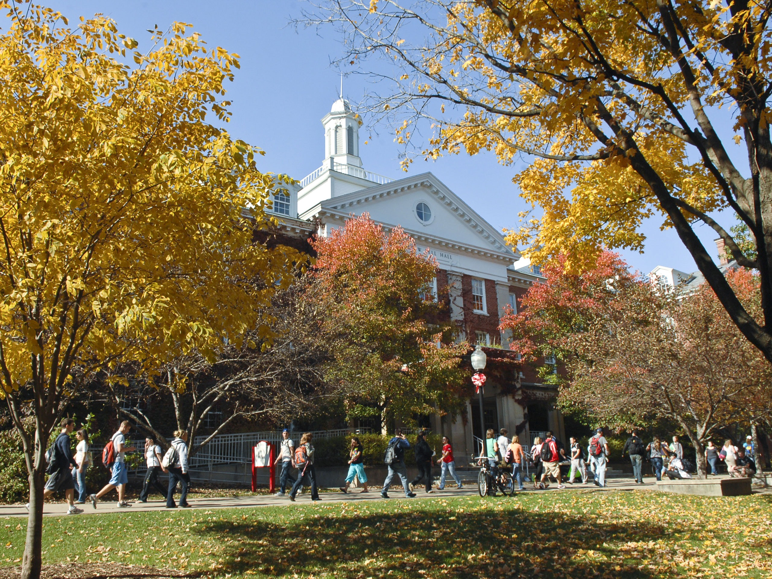 View of Fell Hall in the fall with students walking to class.