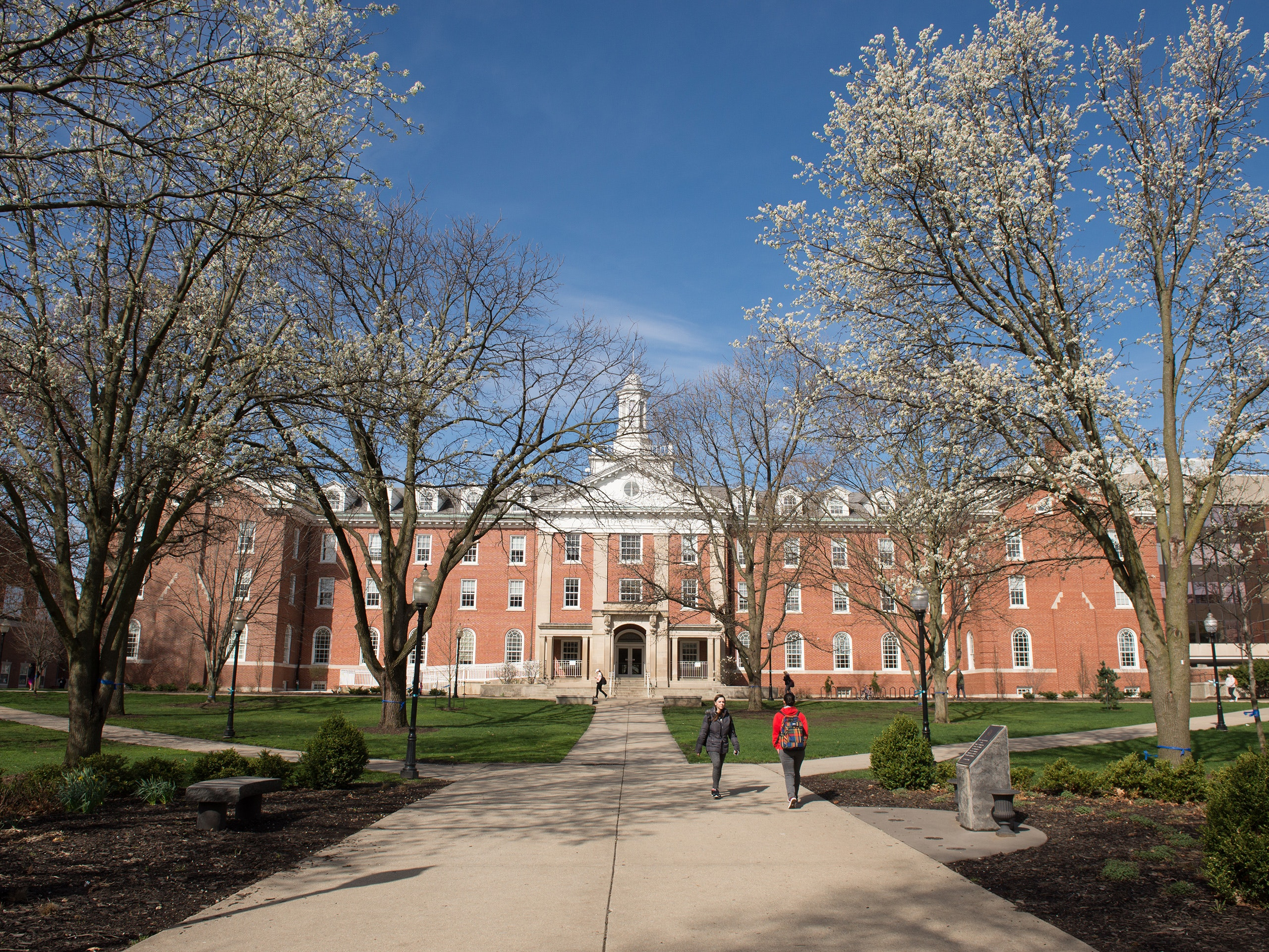 View of Fell Hall with students walking by and flowering trees.